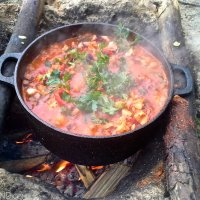 Cooking a meal over fire on a Wild Poland kayaking & camping tour